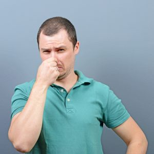 Man holding nose because of dog urine stains and odors